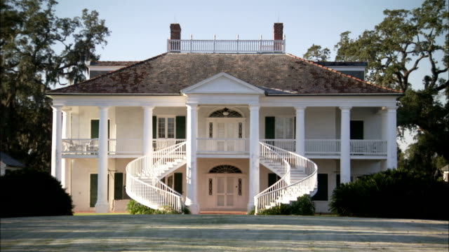 Two staircases curve around the front entrance of a plantation house. Available in HD.