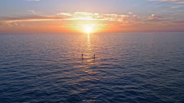 AERIAL zwei aufstehen Paddel-Boarder paddeln am Meer bei Sonnenuntergang