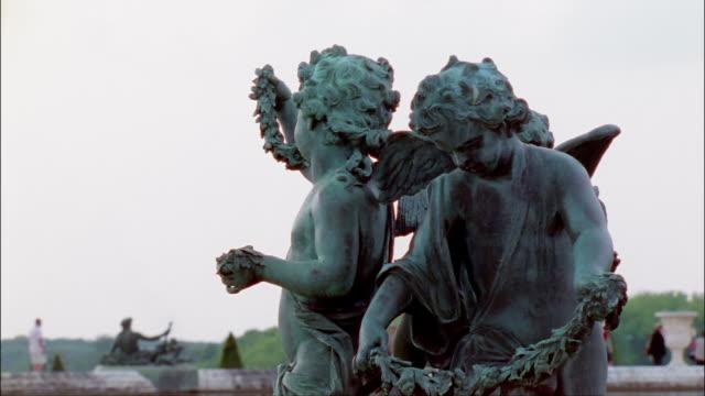 vídeos de stock, filmes e b-roll de cu, two statues of cherubs in garden of palace of versailles, france - 17th century style
