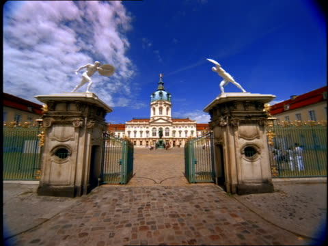 two statues stand on columns at the entryway to the charlottenburg palace in berlin, germany. - palace video stock e b–roll