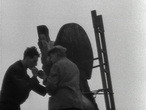 two steeplejacks have a cigarette break on top of nelson's column during its cleaning 1953 - turmarbeiter stock-videos und b-roll-filmmaterial