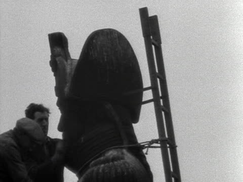 two steeplejacks start to clean the statue of nelson on nelson's column during preparations for the coronation of elizabeth the second 1953 - turmarbeiter stock-videos und b-roll-filmmaterial