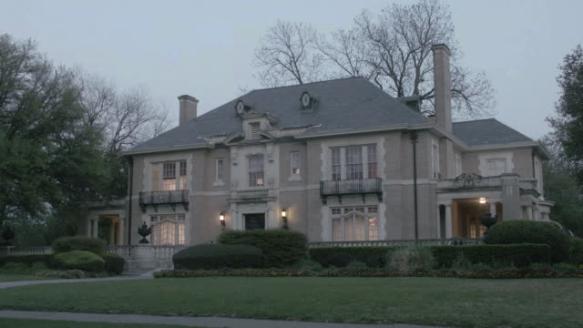 WS Two story colonial estate home with large windows and two chimneys at dusk / United States