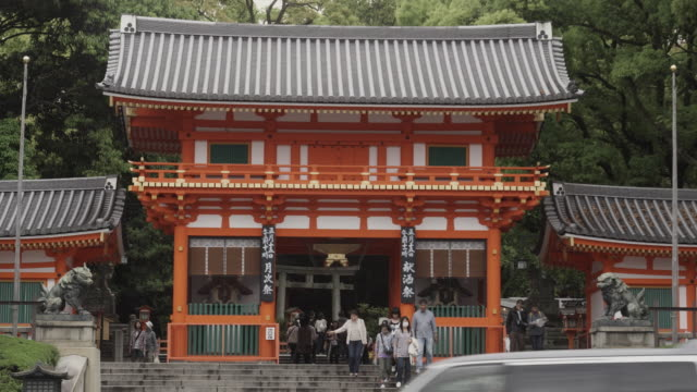 ws two story gateway to yasaka shrine, traffic on street in foreground, gion, kyoto, japan - gion stock videos and b-roll footage