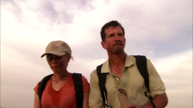 two stranded travelers struggle to walk. - sweat stock videos & royalty-free footage