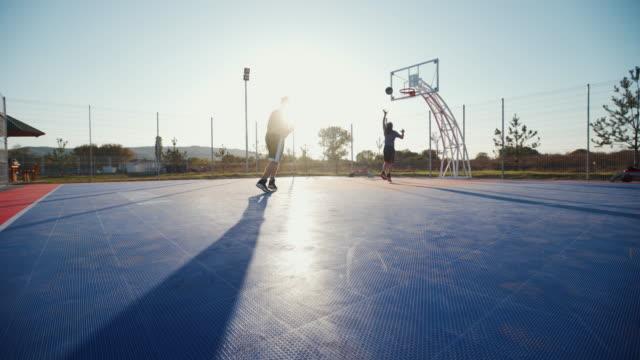 stockvideo's en b-roll-footage met twee straat basketbal spelers opwarmen voorspel - binnenplaats