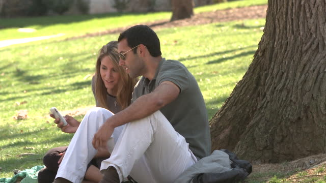 ms two students sitting on campus lawn using mobile phone, bethlehem, pennsylvania, usa - see other clips from this shoot 1503 stock videos and b-roll footage