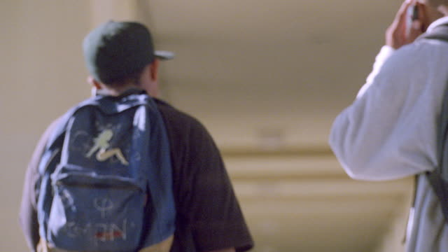 two students use their cellphones as they walk in a corridor. - rucksack stock videos & royalty-free footage