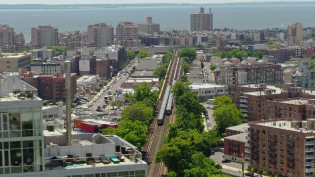 två tunnelbanetåg som åker genom bostadsområdet i brooklyn, new york. drone video med panorering kameran rörelse. - kommunalt bostadsområde bildbanksvideor och videomaterial från bakom kulisserna