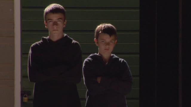 vidéos et rushes de ms two sullen boys standing side by side then walking away / london, england - grognon