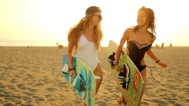 two surfer girl having fun on the beach - female friendship stock videos & royalty-free footage