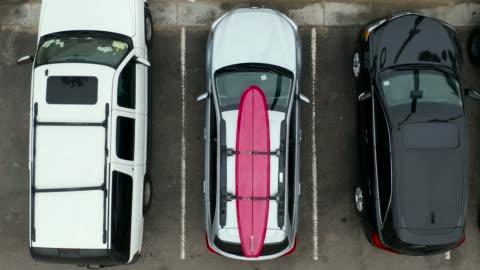 vídeos y material grabado en eventos de stock de dos surfistas descargando surfboard desde roof rack-aerial drone shot - aparcamiento