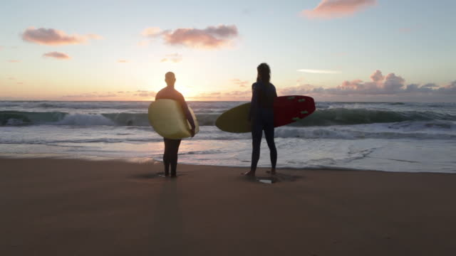 Two surfers with surfboards looking out over waves and toward horizon