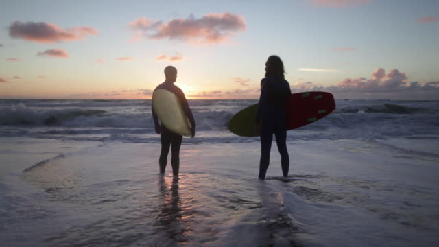 two surfers with surfboards looking out over waves and toward horizon - standing stock videos & royalty-free footage