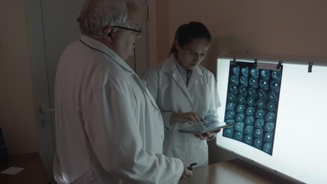 vídeos de stock, filmes e b-roll de dois cirurgiões discutindo tomografia computadorde uma cabeça e uma ressonância magnética de um ombro. a equipe de neurocirurgiões conversando sobre a operação que eles estão prestes a fazer enquanto olham para as tomografias de um paciente... - cirurgião