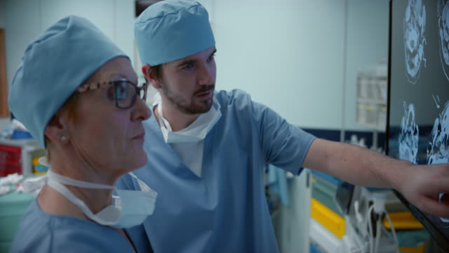 two surgeons discussing ct scan of a head - operating theatre stock videos & royalty-free footage