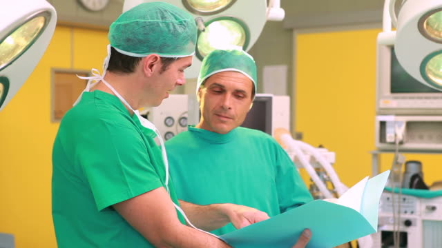 two surgeons smiling while holding files in a surgery theater - chirurgenkappe stock-videos und b-roll-filmmaterial