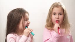 Two sweet little girls cleaning their teeth with a toothbrush and smiling