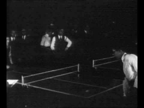 vídeos de stock, filmes e b-roll de two tables of pingpong games with men playing in 1930 tournament and spectators behind / men and women watch applaud from behind net / rear shot man... - tênis de mesa
