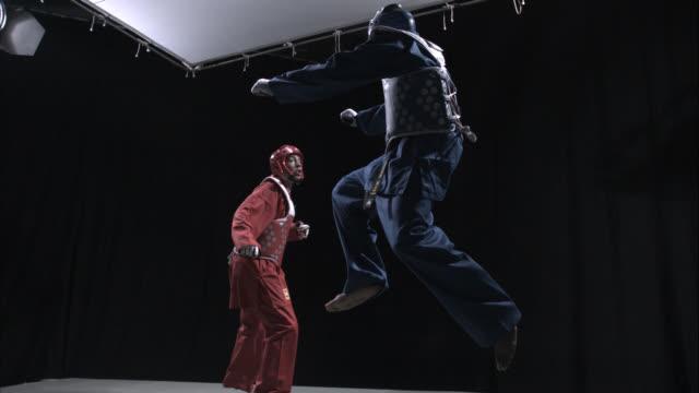 two taekwondo athletes spar in a studio. - taekwondo stock videos & royalty-free footage