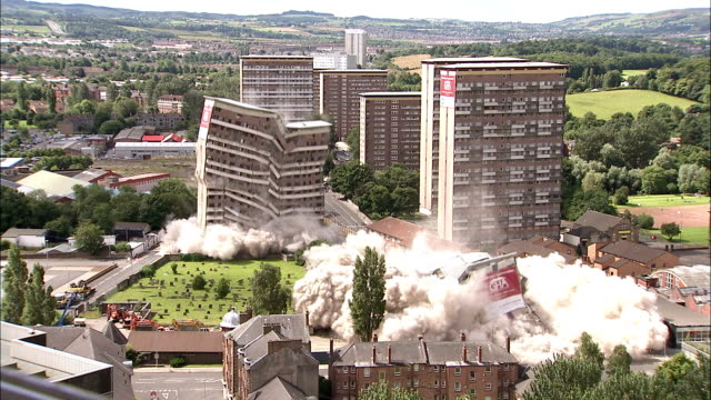 ws two tall apartment buildings are demolished in controlled implosions using explosives and dissappear in huge cloud of dust / pollokshaws, scotland, uk - demolished stock videos and b-roll footage