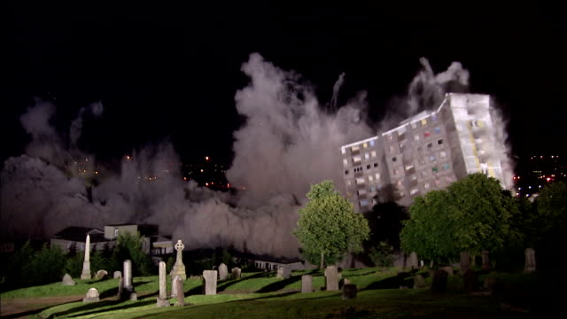 WS  Two tall apartment buildings are demolished in controlled implosions using explosives and dissappearing huge cloud of dust in night / Sighthill, Scotland, UK