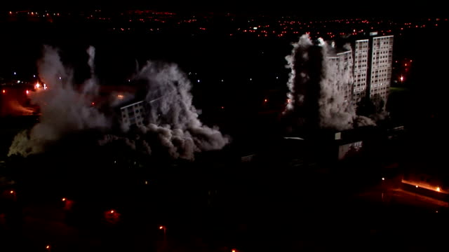 ws  two tall apartment buildings are demolished in controlled implosions using explosives and dissappearing huge cloud of dust in night / sighthill, scotland, uk  - imploding stock videos and b-roll footage