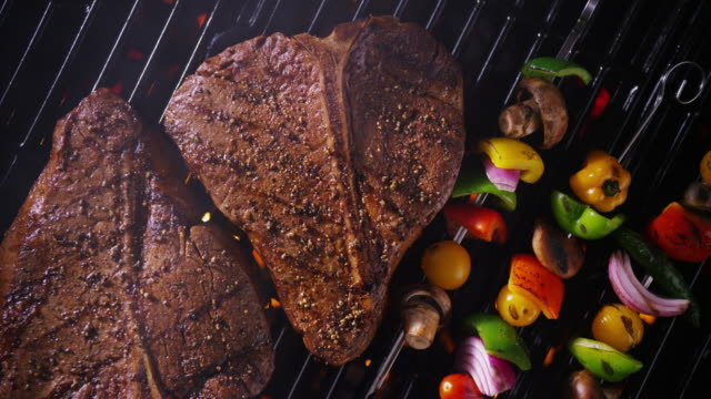 Two T-bone steaks on a grill - camera rotates overhead.