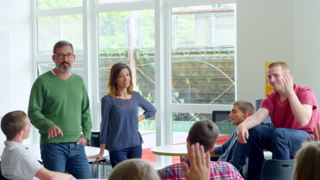 ms two teachers standing in front of high school students with raised hands answering questions. - gelegenheit stock-videos und b-roll-filmmaterial