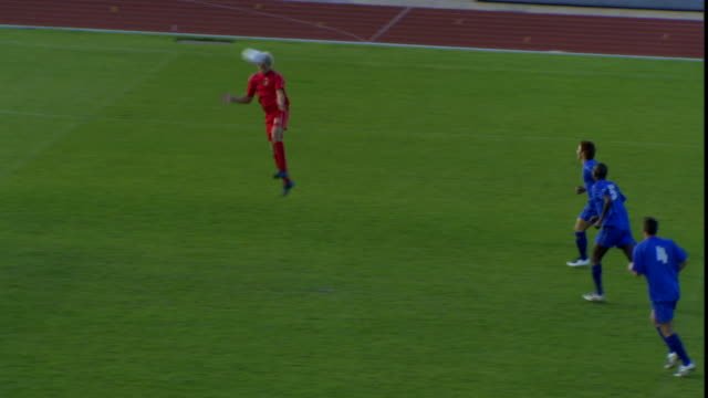 HA WS PAN Two teams playing soccer on field, then red team player head balls to score goal / Sheffield, England, UK