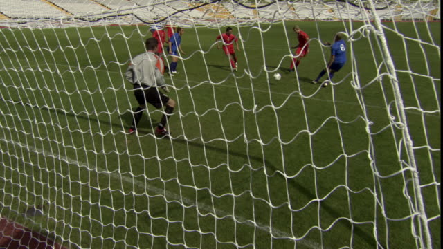 HA WS Two teams playing soccer on field, then red team scores goal / Sheffield, England, UK