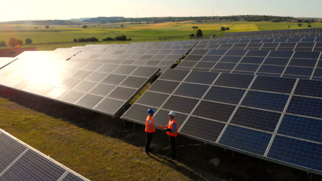 two technicians at solar power station aerial shot - quality control stock videos & royalty-free footage