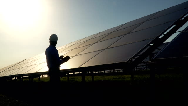 two technicians discussing at solar panel station - riflesso video stock e b–roll
