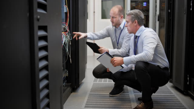 ds two technicians squatting in the server room discussing connections - network server stock videos & royalty-free footage