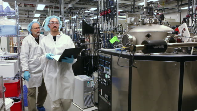 ms pan two technicians walking in laboratory (research and development of solar energy conversion materials) / ann arbor, michigan, united states  - renewable energy stock videos & royalty-free footage
