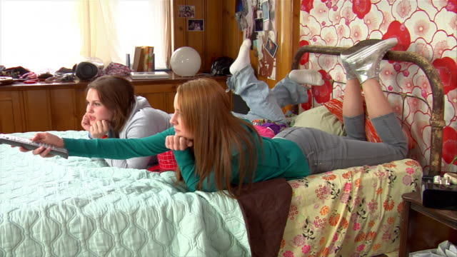 vidéos et rushes de ws ds two teen girls holding remote control and watching tv in bedroom / brooklyn, new york, usa - seulement des jeunes filles
