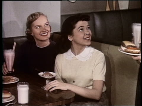 vidéos et rushes de 1954 two teen girls in malt shop smiling as boy with hamburger sits down next to them - unhealthy eating