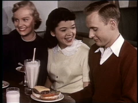1954 two teen girls in malt shop smiling + talking to boy sitting next to them with milkshake - smoothie stock videos & royalty-free footage