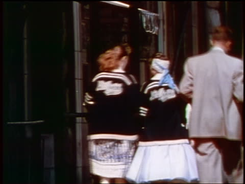 1957 rear view two teen girls in school jackets + man in suit walking on sidewalk / feature - 1957 stock videos & royalty-free footage