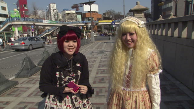 MS Two teen girls wearing costumes on street, Tokyo, Japan