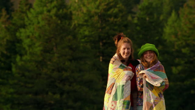 PORTRAIT two teen girls wrapped in quilt laughing + smiling outdoors / pine trees in background / Montana