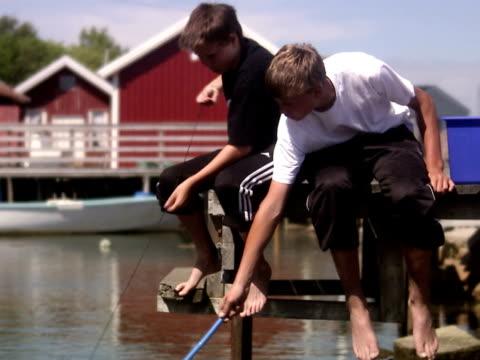 Two teenage boys fishing crab Smogen Bohuslan Sweden.