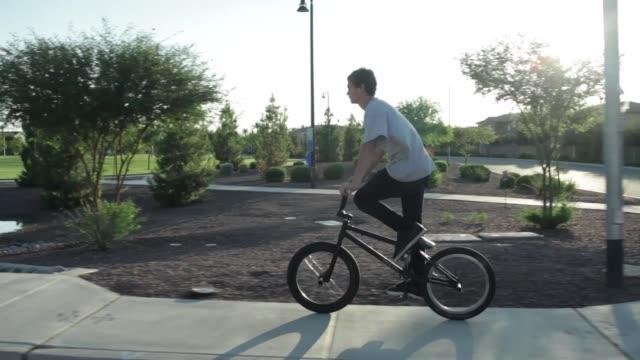 two teenage boys riding their bmx bikes through the suburbs - footpath stock videos & royalty-free footage