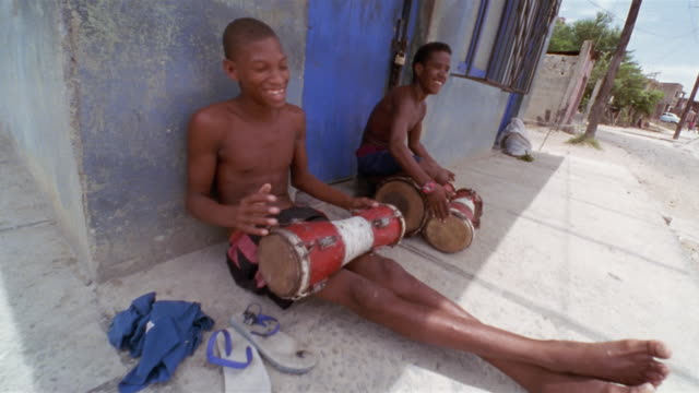 vidéos et rushes de zi, cu, two teenage boys (16-17) sitting on sidewalk and playing drums, santiago de cuba, cuba  - drummer