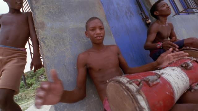 vidéos et rushes de cu, ds, two teenage boys (16-17) sitting on sidewalk and playing drums, santiago de cuba, cuba  - drummer