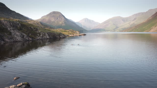 two teenage boys wild swimming in wastwater at dusk - named wilderness area stock videos & royalty-free footage