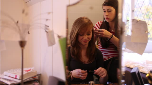 two teenage girls getting ready, reflected in mirror - beauty treatment stock videos & royalty-free footage