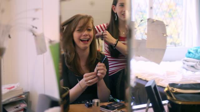 two teenage girls getting ready, reflected in mirror - マルチメディア点の映像素材/bロール