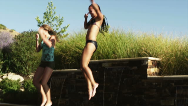 vídeos y material grabado en eventos de stock de slo mo ws two teenage (16-17) girls jumping into swimming pool, american fork, utah, usa - 16 17 años