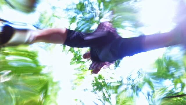 Zwei Mädchen im Teenageralter springen über dem Bach im Wald, einer nach dem anderen. Ungewöhnliche Sicht Kopf, Blick nach oben von der Unterseite des Flusses durch die Wasseroberfläche.